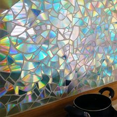 If you still have some old CDs lying around, here's a unique way to use these to create a shimmering bathroom or kitchen backsplash.
