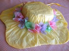 Pretty Easter bonnet is fun to make and will look fabulous on your little one. You'll need painter's hat, plastic wrap, poster board, tissue paper and ribbon. For ages 5 and up. #Crafts #Kids #Hat #Dress_up