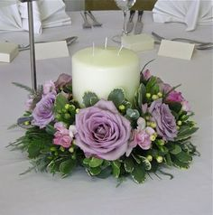 pinks and mauves using roses, freesias, berries and mixed foliages around a chunky multiwick candle