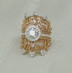This stunning 1.75 ct. diamond engagement ring will sweep her off her feet. Bright and beautiful center stone is surrounded by a sparkling halo. Intricate scroll work through out the piece, studded with diamonds, this ring glows. 14K Rose & White gold. Unique & breathtaking.   Center Stone: Diamond Weight: 1.00 ct Color: G Clarity: SI1 Shape: Round   Side Diamonds: Diamond Weight: 0.75 ct Color: G/H Clarity: SI1 Shape: Round  Sizes available: 3.5-10 (Larger and smaller sizes are ...