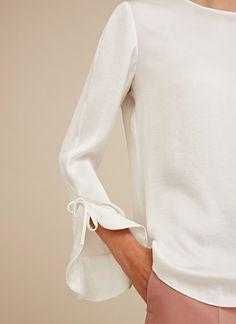Camisa de cuello redondo con manga acampanada y lazada lateral. Textura ultra suave, silueta relajada, bajo ligeramente redondeado y cierre de lágrima en la espalda.