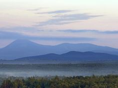 Early morning haze colors Mount Katahdin and its surrounding mountains as seen in 2014 from a height of land along Route 11 in Patten, Maine. The viewpoint is part of the Katahdin Woods & Waters scenic byway.