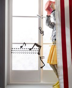 A little girl dances in front of a window with musical notes hung in front of it.