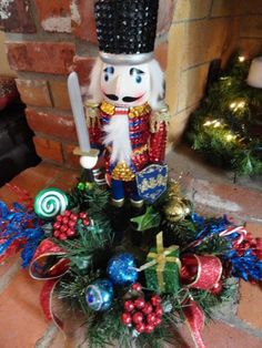 """""""With the large nutcracker, I hot glued a small ring of greenery around it and use Christmas picks and ribbon to decorate it.  The candy canes and ribbon candy used for the centerpiece were from Dollar Tree.  I tried to make the centerpiece with as much bright color and sparkle as I could.  After all, what kid doesn't like color and sparkle?"""""""