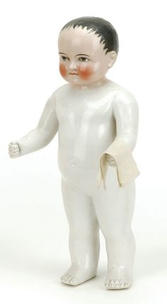 "Germany, ca. 1880, large one piece white china body with pink luster head, with black molded and painted brush stroked hair, brown painted eyes with radiating irises, nicely sculpted torso with clenched fists Size: 13"" t."