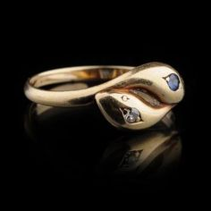 "Gold Ring, set with a brillant and sapphire, 1st half of the 20th century. 14k Gold. Bezel in the shape of intertwined snakes' heads, one set with a brilliant, the other set with a sapphire. In the ring, hallmark ""585"", and the goldsmith's mark (illegible) D. 16 mm / Size (FR) 51 Weight: 2,15 g."
