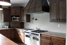 Rustic range hood, commercial range, walnut cabinets, stained concrete