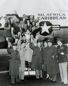 """North Africa Caribbean USO troupe departs after a Camp Show Christmas Special, 16 December, 1955. Pictured center is George Murphy, President of the Hollywood Coordinating Committee, which was originally formed in 1941 under the name the Hollywood Victory Committee, and was charged with arranging for screen stars to attend bond drives, entertain in USO shows, and perform other """"morale-boosting"""" activities. Coralie Hewitt Tillack Collection. San Fernando Valley History Digital Library"""