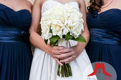 Navy blue gowns with a white gardenia bouquet.