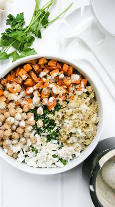 Healthy Kale Salad Bowl with Tahini, Roasted Sweet Potatoes, Quinoa, Feta, and Chickpeas: meatless and filling.