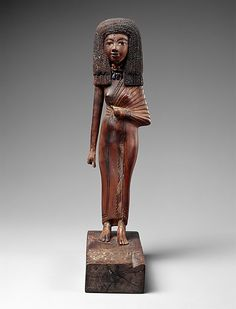 Statuette of the lady Tiye.  Period:     New Kingdom Dynasty:     Dynasty 18 Reign:     reign of Amenhotep III–Akhenaten Date:     ca. 1390–1349 B.C. Geography:     Egypt Medium:     Wood, carnelian, gold, glass, Egyptian blue, paint