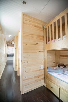 The kids' room in the Hogan's Haven tiny house. Bunk beds give each child their own space, while fitting neatly into a compact area that still offers plenty of floor space for playtime. #tinyhouse #happytiny