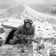 A soldier from the 1st Battalion Rifle Brigade, 7th Armoured Division, emerges from his foxhole armed with a PIAT, 28 December 1944.