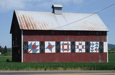Barn with quilts painted on the side, I think this would be cool to paint the block walls in the backyard.
