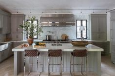 Exquisite contemporary gray kitchen boasts three brown leather weave barstools placed in front of a gray center island topped with a thick marble countertop finished with a stainless steel  prep sink and a satin nickel gooseneck faucet.
