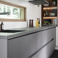 Super Matt Grey kitchen units add an ultra modern feel. Illuminating the handle recesses looks fantastic for mood lighting at a dinner party - Halton by First Impressions
