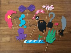 DIY Mermaid or Pirate Gender Reveal Party Photo Props! I used cardstock to cut these by hand and embellished with Stickles glitter glue, rhinestones, and wooden skewers for the sticks. #mermaid #pirate #photobooth #photoprop #diy #clamshell #octopus #beard #mustache