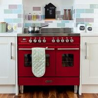 Country kitchen with red range cooker and pastel wall tiles