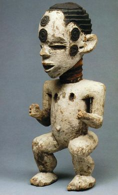 Boki Provenience: Nigeria Cross River Section: African Materials: Wood Pigment Iconography: Cicatrisation Description: Wooden figurine painted white except for hair. Two raised discs on forehead and each temple, which are black, together with the eyes. Neck carved with rings, red yellow and black.