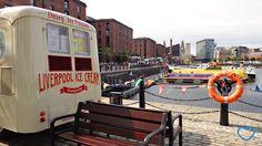 """No enquadramento, está a parte traseira e uma komvi, onde está escrito """"Liverpool ice cream"""". Ao fundo, a cidade de Liverpool."""