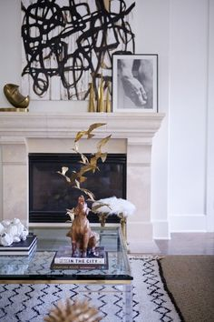 very chic ...a moroccan beni ourain carpet with a black & white abstract painting over the marble fireplace