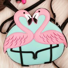 Sleepville Critters Flamingo Crossbody Leather Love is in the air. Beautiful Crossbody Purse Sleepville Critters Flamingo Birds Bag.  Finely stitch crafted, with a full size design flamingos in pink,  black,  and white. In a mint color background,  back is in black color.  Design exclusively for a fashion hurry day, or night out. Fits keys,  lipstick, cards,  and cell phone.  Back slot for easy receipt access, or cards. Size: Sleepville Critters  Bags Crossbody Bags