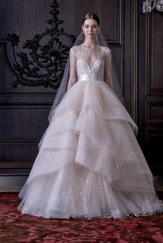 This Monique Lhuillier ballgown, with a tiered skirt, belted waist, deep sweetheart neckline, and sheer sleeves, is a dream. Come see 30 other wedding dresses with sleeves you'll fall for
