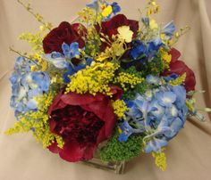 This is a cube vase floral arrangement that features red peonies and blue hydrangea with yellow accents of oncidium orchids and solidago.  See our entire selection at www.starflor.com.  To purchase any of our floral selections, as gifts or décor, please call us at 800.520.8999 or visit our e-commerce portal at www.Starbrightnyc.com. This composition of flowers is generally available for same day delivery in New York City (NYC). SQ200