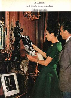 Mohammad Reza and Farah Pahlavi in 1961 looking at family pictures and a portrait of French President General De Gaulle on their side.