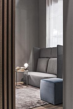 Lampadina designed by Achille Castiglioni adds a bright glow to this modern, intimate living room featuring with a blue ottoman and a gray sofa. Explore Lampadina & more FLOS favorites on the FLOS USA website.