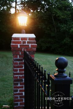 Our luminous 4 foot Stronghold Iron Fence lit up by a brick pillar and lamp