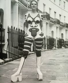 """""""Artist, journalist and political activist Caroline Coon models white platform zip-up boots and a hand-knitted graphic jumpsuit with tight hooped leggings with bloomer effect by Kansai Yamamoto in 1971. Yamamoto went on to design the Ziggy Stardust outfits for David Bowie."""" - sourced from Vintage Fashion by Ottlie Godfrey"""