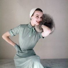 Model is wearing a Heller baby blue worsted jersey dress with taffeta lining and satin bow at neck by Richard Cole. 1952