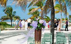 Tiki torches filled with floral at Disney's Castaway Cay wedding ceremony