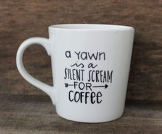 """This listing is for one white, high-quality ceramic coffee mug with the words, """"A Yawn is a Silent Scream for Coffee"""" and a small arrow detail."""