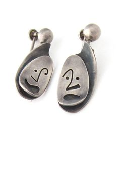 """by: Phyllis Sklar, ca 1960 material: sterling silver size: 1 1/2"""" x 5/8"""" These whimsical earrings by American Modernist Phyllis Sklar feature hand cut faces set in relief above nicely patinated curved"""
