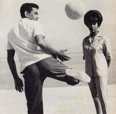 Garrincha de calça, sapato e camisa, brinca sob os olhares de Elza Soares.