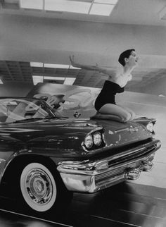 NY Auto Show, December 7th, 1956  Model Jean Littleton in a strapless swimsuit, posing as a hood ornament on the front of a new De Soto convertible on a rotating platform at the New York Coliseum auto show.