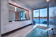 Seaside bathroom features full height sliding glass patio access, with wall-mounted waterfall faucet above large soaking tub standing across a marble tile floor from immense dual vanity, wrapped in glossy white cabinetry.