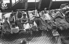 Fotografia z Powstania Warszawskiego. Ranni leżący na korytarzu powstańczego szpitala, prawdopodobnie w budynku PKO (?)