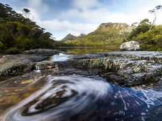 Water swirls from Wombat Pool in Cradle Mountain-Lake St Clair National Park in Tasmania, Australia. Located in Tasmania's central highlands, the park features craggy peaks, a glacial lake, and dense old-growth forests.