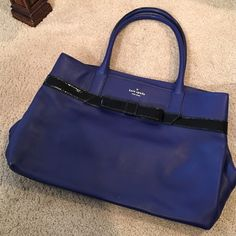 Kate Spade Blue Handle Tote w/Black Bow Detail Authentic Kate Spade gorgeous blue top handle satchel featuring front and back black bow detail, front KS gold logo, gold tone feet, interior separated into two sides by a middle zipper pouch, interior side zip pocket (price tag inside), and two side interior pockets as well as interior polka dot material. Like new, only signs of wear on some on two bottom corners. No dust bag. No trades, best offers usually accepted. kate spade Bags Satchels