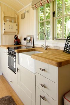A farm sink, butcher block counter, and an electric range can be found in the kitchen.