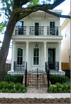 wrought iron railing panels between wood columns over the front porch-  from Cote de texas blog