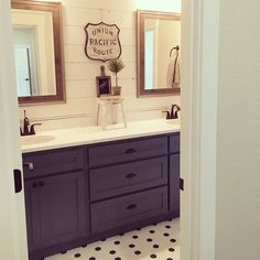 Blue cabinets are a fun splash of color in this modern farmhouse kids bathroom. The blend of reclaimed wood, black & white hex tile, and shiplap add instant charm. Interior design by Janna Allbritton of Yellow Prairie Interior Design.