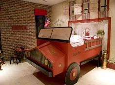 WOW!!! This bedroom has a vintage fire truck bed and walls decorated with the name of the fire station. Little details like the brick wall an metal fire extinguisher complete he look.
