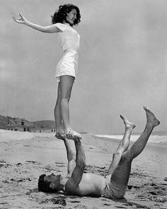 Ava Gardner & Burt Lancaster doing acro yoga on the beach.