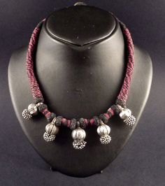 "Beautiful old necklace from Rajasthan, India. The five small pendants were originally head ornaments and they are massive and heavy good silver. It has been recently strung with black and red cotton cord. These forehead pendant ornaments were handmade using a traditional decorative technique called ""goli"", small silver balls which are not welded to the base, but attached with a wire, giving them some slight movement."