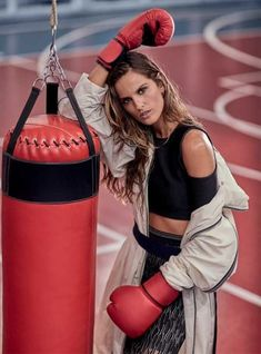 Izabel Goulart rocks some boxing gloves with crop top and high-waisted skirt