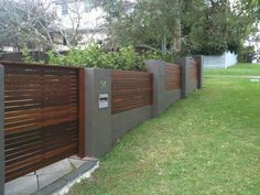 Brick & horizontal timber fence on sloping ground